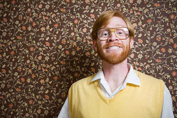 Retro Nerd and Vintage Wallpaper A man in 1960's-1970's style stands in his floral vintage wallpaper living room smiles for a portrait. Horizontal with copy space. nerd stock pictures, royalty-free photos & images