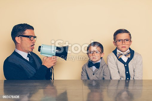 992091590 istock photo Retro Nerd Children not Listening to Dad 992476408