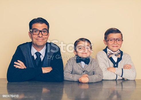 A father and his sons in nerd outfits are cheesy smiling at the camera. These boys love bonding over being smart together. The father is raising his sons to be the next generation of intellectual geniuses.
