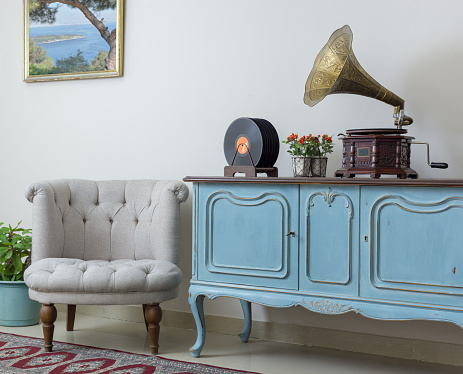 Retro off white armchair, vintage wooden light blue sideboard, old phonograph (gramophone) and vinyl records on background of beige wall, tiled porcelain floor, and red carpet