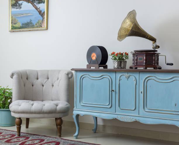retro aus weißen sessel, vintage leichte blaue anrichte aus holz, alte plattenspieler (gramophone) und vinyl-schallplatten auf hintergrund beige wand, porzellan gefliesten boden und roten teppich - hellblaues zimmer stock-fotos und bilder