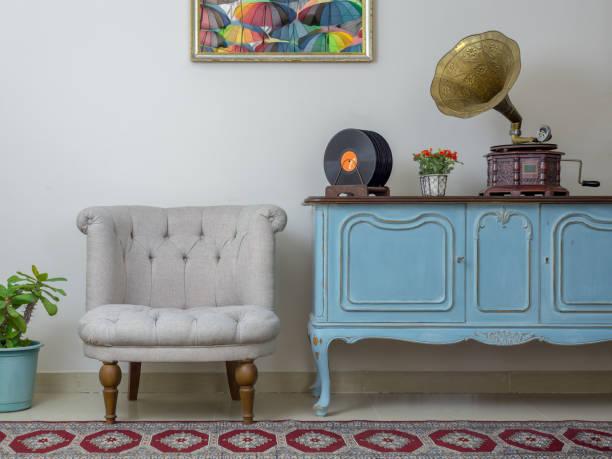 retro aus weißen sessel, vintage leichte blaue anrichte aus holz, alte plattenspieler (gramophone) und vinyl-schallplatten auf hintergrund beige wand, porzellan gefliesten boden und roten teppich - teppich hellblau stock-fotos und bilder