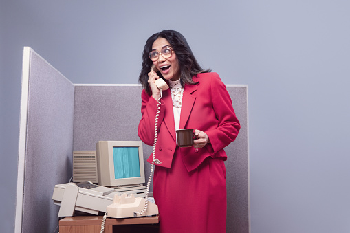 A vintage Filipino business woman at the office works at an old computer at her cubicle desk.  1980's - 1990's fashion style.