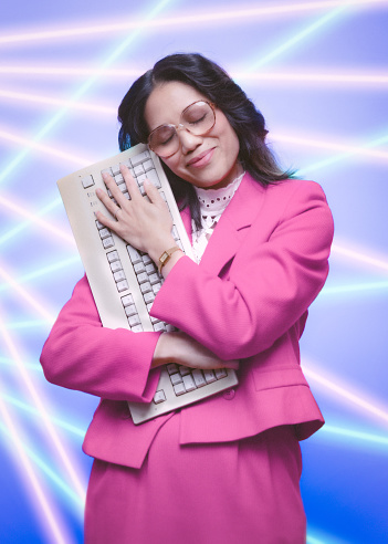 A portrait of a vintage Filipino business woman in retro style, hugging a computer keyboard.  Glamour shot type portrait.  1980's - 1990's fashion style.