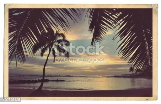 A Retro 40s-50s style antique postcard with a surfer on a tropical beach.