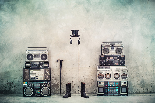 istock Retro old design ghetto blaster boombox radio cassette tape recorders, headphones, cylinder hat, leather boots, walking stick cane front concrete street wall. Vintage style filtered conceptual photo 1057679542