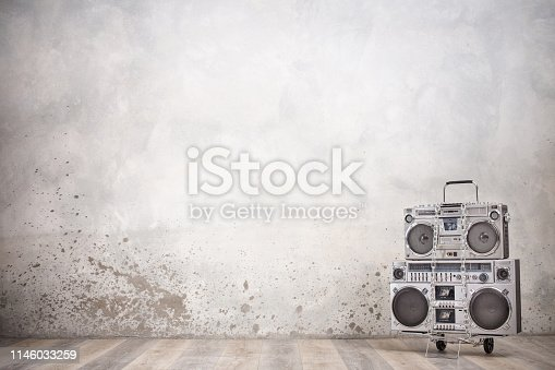 1043737676 istock photo Retro old design ghetto blaster boombox stereo radio cassette tape recorders from circa 1980s on handcart front concrete wall background. Rap and Hip Hop music concept. Vintage style filtered photo 1146033259