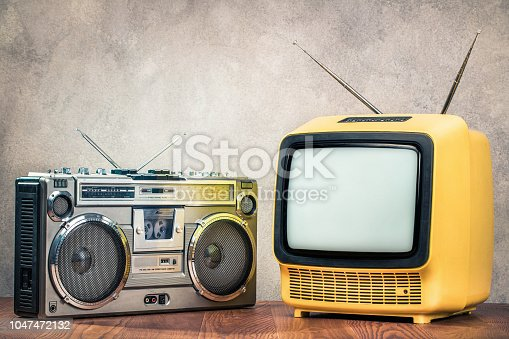 1056306726istockphoto Retro old designed tube TV receiver and ghetto blaster stereo radio cassette tape recorder boombox from circa late 70s front concrete wall background. Vintage nostalgia style filtered photo 1047472132