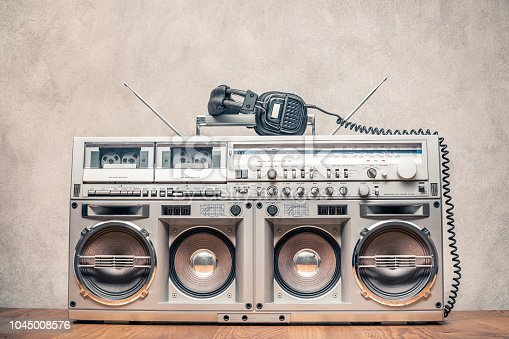 1043737676 istock photo Retro old ghetto blaster stereo radio cassette tape recorder boombox from circa 1980s and headphones front concrete wall background. Vintage instagram style filtered photo 1045008576