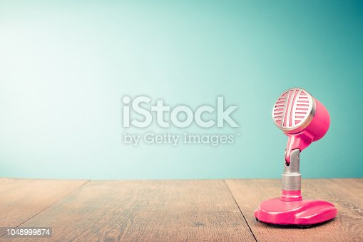 1043737676 istock photo Retro old microphone from 60s front mint green background. Vintage style filtered photo 1048999874