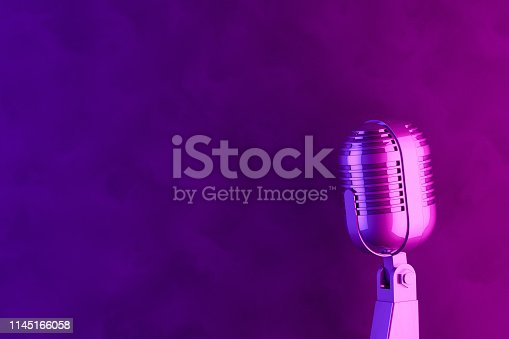 Old style microphone with retro background, color gradient. Vintage concept. Neon lights.