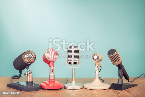 istock Retro old microphones for press conference or interview on table. Vintage style filtered photo 1048966212