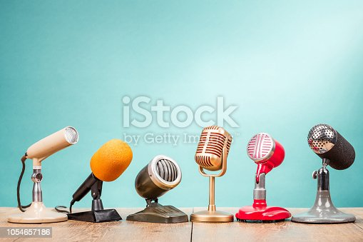 istock Retro old microphones for press conference or interview on table front gradient aquamarine background. Vintage old style filtered photo 1054657186