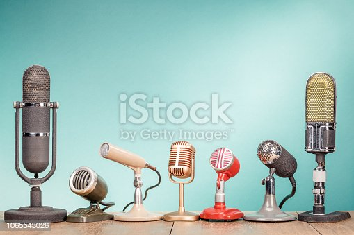 1065736660 istock photo Retro old microphones for press conference or interview on wooden desk front gradient mint green background. Vintage style filtered photo 1065543026