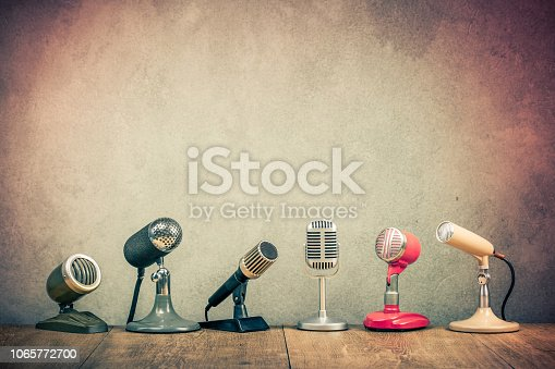 1065736660 istock photo Retro old microphones for press conference or interview on wooden desk. Vintage instagram style filtered photo 1065772700