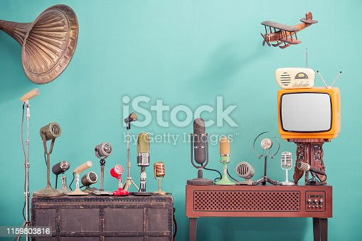 istock Retro old microphones for press conference or interview, outdated TV, radio, flying wooden toy plane and gramophone horn front gradient aquamarine wall background. Vintage old style filtered photo 1159803816