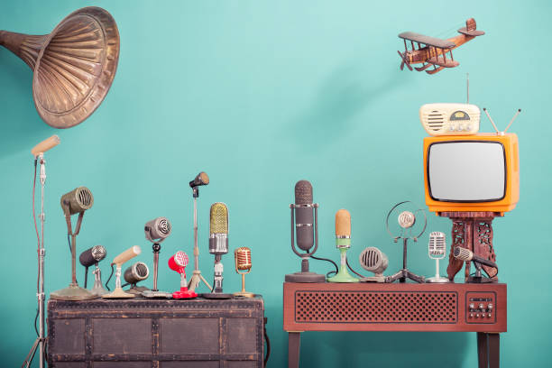 retro old microphones for press conference or interview, outdated tv, radio, flying wooden toy plane and gramophone horn front gradient aquamarine wall background. vintage old style filtered photo - trasmissione radiofonica foto e immagini stock