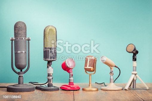 istock Retro old microphones for press conference or interview recording on table front gradient aquamarine background. Vintage old style filtered photo 1051138940