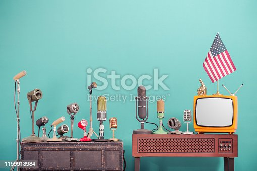 istock Retro old microphones from 50s and 60s for press conference or interview, outdated TV from 70s, USA flag, golden index finger front gradient aquamarine  wall background. Vintage style filtered photo 1159913984