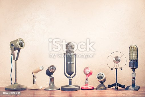 istock Retro old microphones on table. Vintage style filtered photo 1049358668