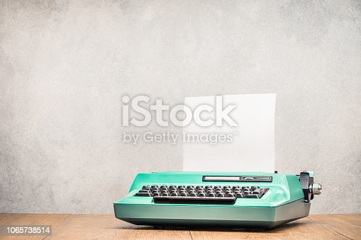 istock Retro old mint green typewriter with paper blank on wooden table front concrete wall background. Vintage style filtered photo 1065738514
