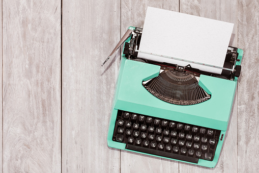 Retro old mint green typewriter with paper sheet on wooden table