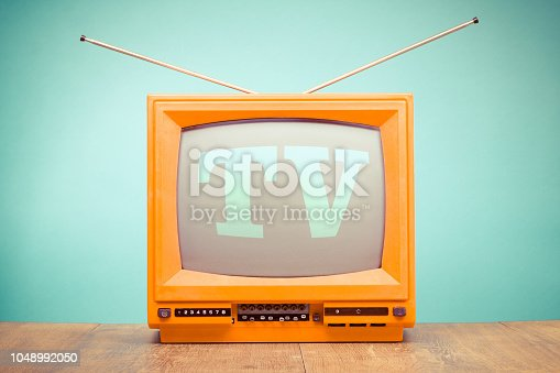 istock Retro old orange TV receiver on table front mint green wall background. Vintage style filtered photo 1048992050