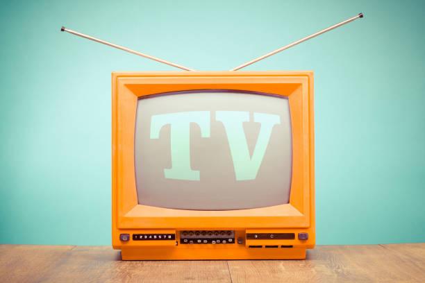Retro-alte orange TV Receiver auf Tabellenhintergrund vorderen Minze grüne Wand. Vintage-Stil gefilterten Foto – Foto