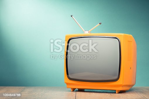 1056306726istockphoto Retro old orange TV receiver on the table front textured gradient mint green background. Vintage style filtered photo 1054649788