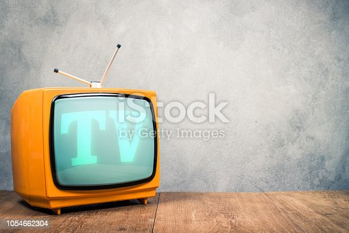 istock Retro old orange TV receiver on wooden table front textured concrete wall background. Vintage instagram style filtered photo 1054662304