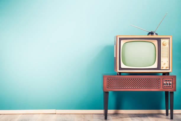 Retro alte veraltete klassische TV-Empfänger mit TV-Antenne aus ca. 60s of XX Century auf Holzständer mit Verstärker front Gradient mint blau Wandhintergrund. Vintage-Stil gefiltertfoto – Foto
