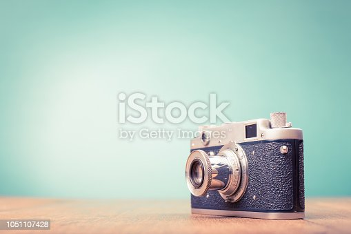 istock Retro old outdated rangefinder film camera from 50s on table front mint green background. Vintage style filtered photo 1051107428