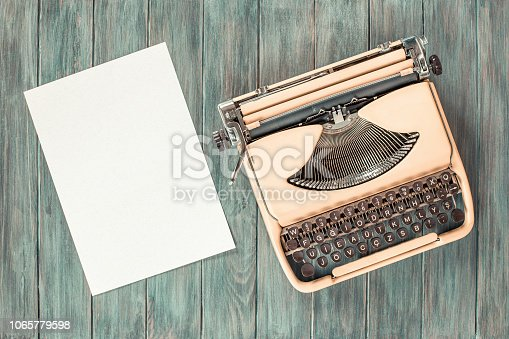 istock Retro old portable compact typewriter circa 70th and paper sheet blank on mint green grunge wooden desk. Vintage style filtered photo 1065779598