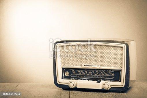 1065736660istockphoto Retro old radio on table. Vintage style sepia photo 1053631514