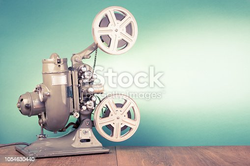 istock Retro old reel movie projector for cinema. Vintage style filtered photo 1054630440