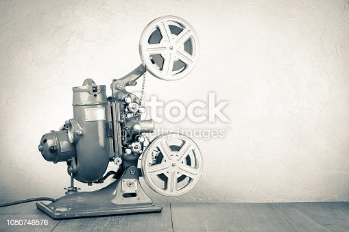 istock Retro old reel movie projector for cinema. Vintage style sepia photo 1050746576