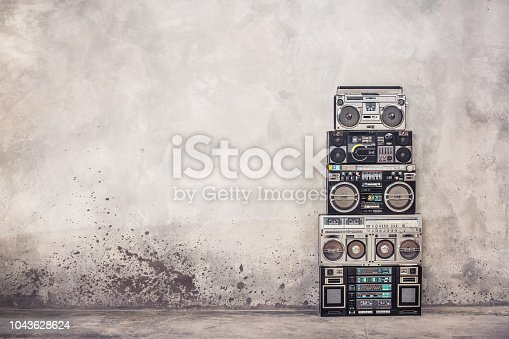 istock Retro old school design ghetto blaster boombox stereo radio cassette tape recorders tower from circa 1980s front concrete wall background. Vintage style filtered photo 1043628624