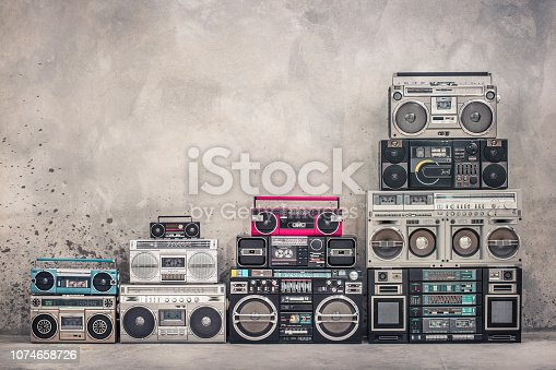 istock Retro old school design ghetto blaster boombox stereo radio cassette tape recorders tower from circa 1980s front aged concrete wall background. Vintage style filtered photo 1074658726