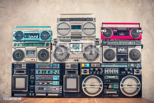 1043737676 istock photo Retro old school design ghetto blaster stereo radio cassette tape recorders boombox tower from circa 1980s front concrete wall background. Vintage instagram style filtered photo 1043809546