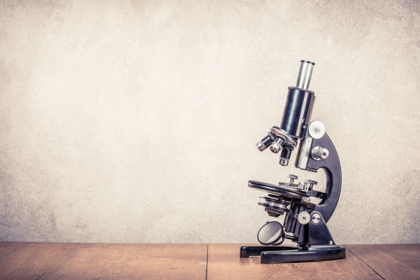 Retro old scientific laboratory microscope circa 40s on wooden table front concrete wall background. Vintage style filtered photo Retro old scientific laboratory microscope circa 40s on wooden table front concrete wall background. Vintage style filtered photo 20th century stock pictures, royalty-free photos & images