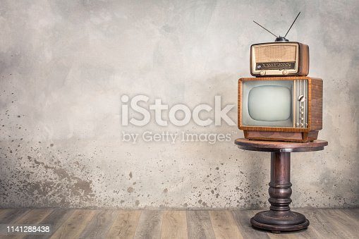 istock Retro old TV receiver and outdated broadcast radio from circa 50s on wooden table front textured concrete wall background. Vintage style filtered photo 1141288438