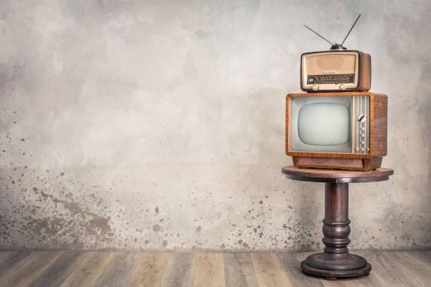 Retroalter Fernsehempfänger und veraltetes Rundfunkradio aus ca. 50er Jahren auf hölzerner Tischfront strukturierter Betonwandhintergrund. Vintage-Stil gefiltert Foto – Foto