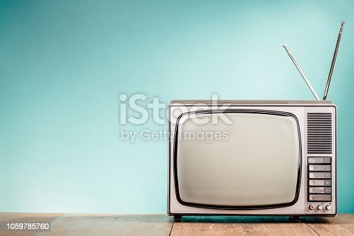 Retro old TV receiver on the table front gradient aquamarine wall background. Vintage style filtered photo