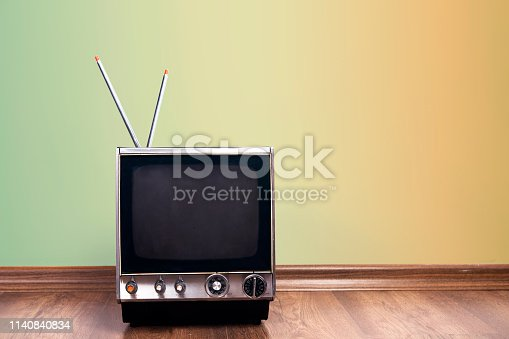 1056306726istockphoto Retro old TV receiver on the table front gradient aquamarine wall background 1140840834