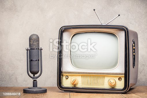 istock Retro old TV set and aged microphone front concrete wall background. Broadcasting concept. Vintage style filtered photo 1056646418