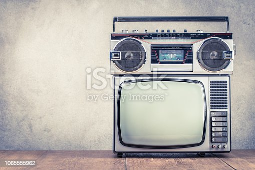 1056306726istockphoto Retro old TV set receiver and radio cassette recorder on table front textured concrete wall background. Broadcasting concept. Vintage style filtered photo 1065555962