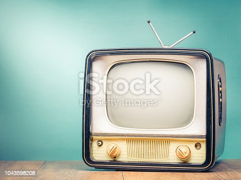 istock Retro old TV set receiver on table front gradient mint green wall background. Broadcasting concept. Vintage style filtered photo 1043598208