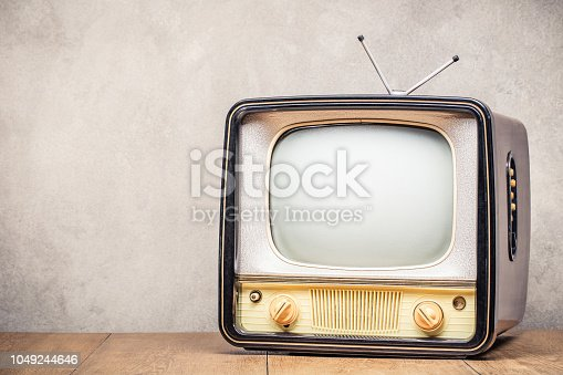 1056306726istockphoto Retro old TV set receiver on table front textured concrete wall background. Broadcasting concept. Vintage style filtered photo 1049244646