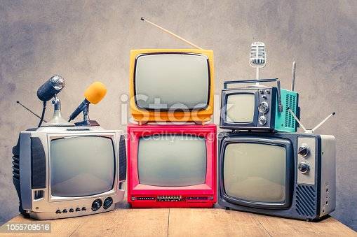 istock Retro old TV set receivers and microphones on table front textured concrete wall background. Broadcasting concept. Vintage style filtered photo 1055709516