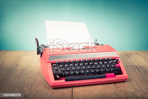 istock Retro old typewriter from 70s with paper blank on wooden table. Vintage style filtered photo 1054095376